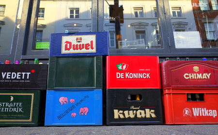 awaiting: London, England - December 28, 2015: Crates of empty beer bottles of various brand names, standing on the sidewalk awaiting collection outside a bar in central London