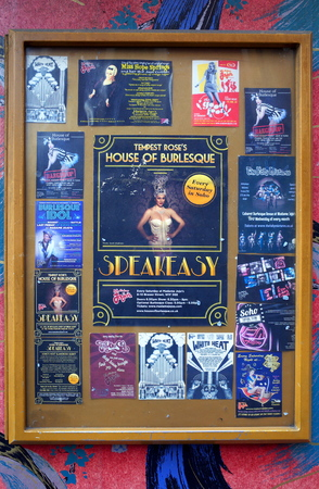 adult entertainment: London, England - December 28, 2015: Glass billboard on a painted wall with posters and flyers advertising burlesque entertainment shows and DJ nights at venues in the Soho district of London, England
