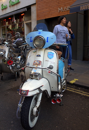 a two wheeled vehicle: London, England - December 28, 2015: People walking by customized Lambretta Motor Scooters parked in the street in the Soho district of London, England