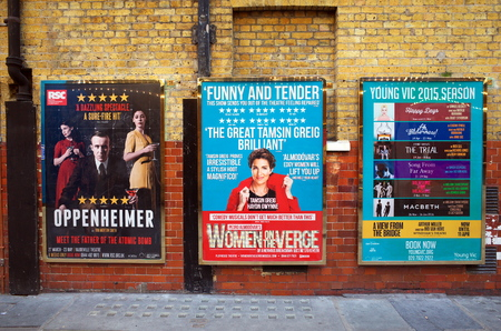 arts culture and entertainment: London, England - April 16, 2015: Billboard posters on a brick wall advertising musicals and plays in the West End of London. In 2013, ticket sales for London theatres were in excess of 500m