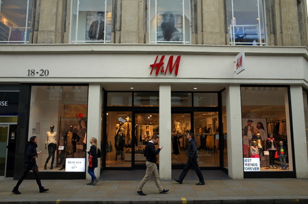 woman shop: London, England - February 04, 2016: People passing by the HM fashion store in Richmond, London. Originally from Sweden, HM opened their first store outside Scandinavia in London in 1976
