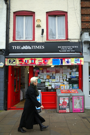 small town life: London, England - February 04, 2016: A pedestrian passes by a typical newsagent store in the town center of Richmond, London UK