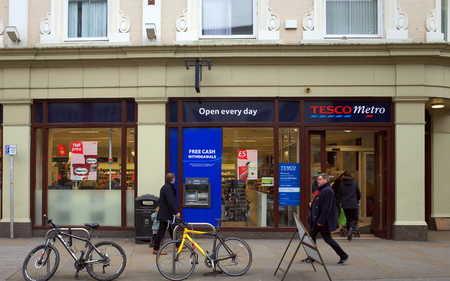 local supply: London, England - February 04, 2016: People passing by and entering the Tesco Metro store in Richmond, London. Tesco was founded in 1919 by Jack Cohen Editorial