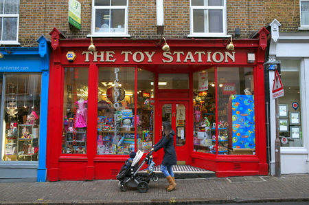 London, England - February 04, 2016: Pedestrian pushing a pram and child past the window display of The Toy Station Store in Richmond, London. The store opened in October 1996