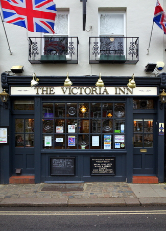 sidewalk: London, England - February 04, 2016: Exterior of the The Victoria Inn public house in Richmond, London. An example of an english pub with Union Jack flags flying above the entrance Editorial