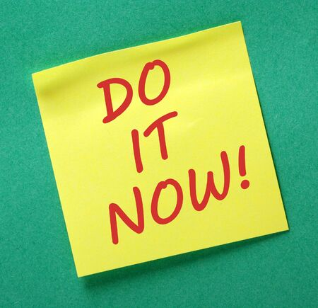 posted: The words DO IT NOW in red ink on a yellow sticky note posted on a green notice board