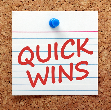 The words Quick Wins in red text on a card pinned to a cork notice board as a reminder Banque d'images