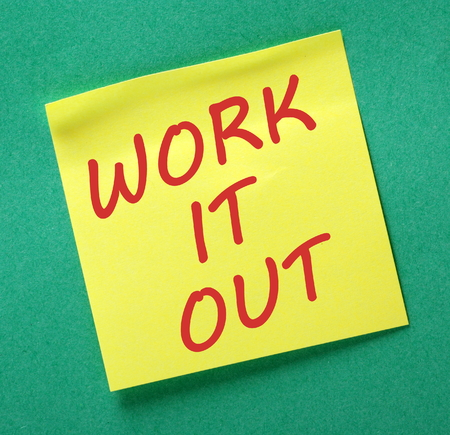 posted: The words Work It Out in red text on a yellow sticky note posted on a green background as a reminder to sit down and discuss problem