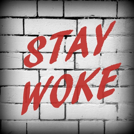 current events: The words Stay Woke in red text on a white brick wall as a reminder to remain aware and stay informed about politics and other issues Stock Photo
