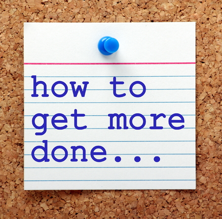 note board: The question how to get more done in blue text on a note card pinned to a cork notice board as a reminder to find ways to increase productivity