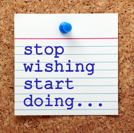 unleash: The words Stop Wishing Start Doing in blue text on a note pinned to a cork notice board as a reminder Stock Photo