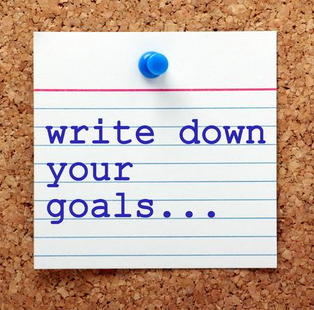 metas: Las palabras escribir sus metas en el texto azul en una tarjeta de nota clavada en un tablón de corcho como un recordatorio