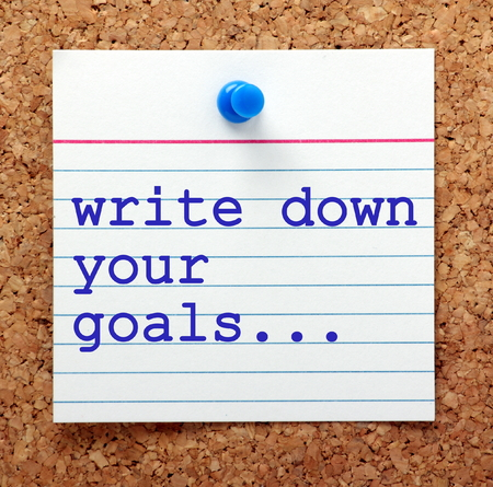 set goals: The words Write Down Your Goals in blue text on a note card pinned to a cork notice board as a reminder Stock Photo
