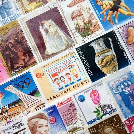postage stamps: LONDON, United Kingdom - JULY 26 2016: Collection of colorful used postage stamps from various countries laid out in orderly rows on a flat surface