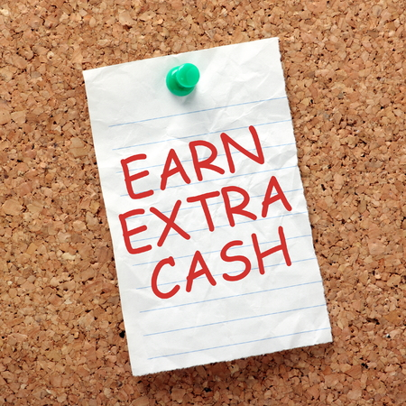 lined paper: The words Earn Extra Cash in red text on a piece of lined paper pinned to a cork notice board as a reminder to find ways to make more money on the side