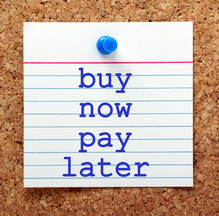 note board: The words Buy Now Pay Later in blue text on a note card pinned to a cork notice board as a reminder to purchase on credit