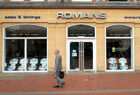 Reading, England - April 23, 2015: A pedestrian in a suit passes by the window display of Romans Estate Agents in Reading, a town in the South East of England Editorial