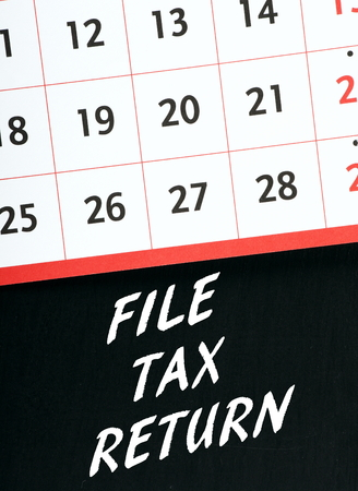 prompt: Calendar on a blackboard with the words File Tax Return as a reminder to submit your personal or business tax details on time