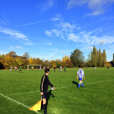 linesman: Bracknell,England - November 13, 2016: An official linesman with his flag keeps his eye on a game of amateur football being played on a sunny Autumn day in Bracknell, England