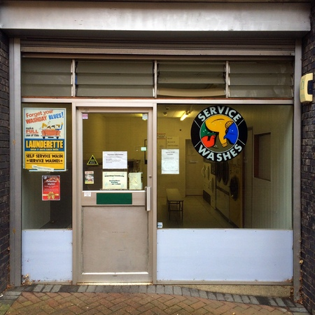 launderette: Bracknell,England - November 14, 2016: Front view of the exterior of a launderette with signs and notices in Bracknell, England during daylight hours