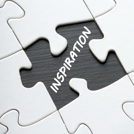 reveals: A missing jigsaw puzzle piece reveals the word Inspiration as a concept for unlocking ideas and solutions