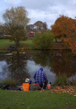 municipal editorial: Bracknell,England - November 23, 2016: People fishing with rod and reel on the banks of a public lake on a cloudy November day in Bracknell, England
