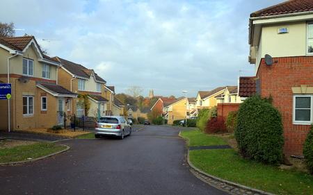case moderne: Bracknell, Inghilterra - 23 novembre 2016: case su un moderno complesso residenziale con macchine parcheggiate in mezzo alla strada e un campanile chiesa in lontananza a Bracknell, in Inghilterra