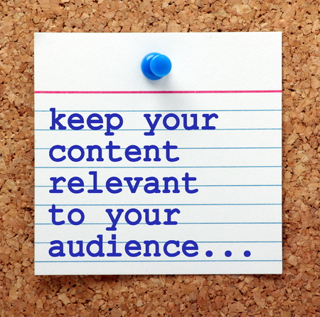 note board: The phrase Keep Your Content Relevant to Your Audience in blue text on a note card pinned to a cork notice board as a reminder for your social media marketing strategy
