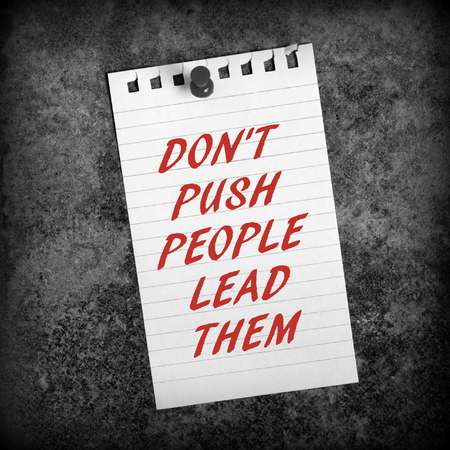 lined paper: The words Dont Push People Lead Them in red text on a sheet of lined paper as a reminder to empower staff to achieve more