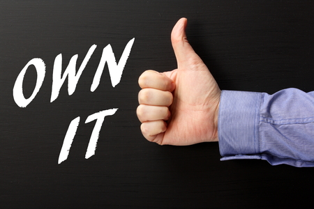 take charge: Male hand in a business shirt giving the thumbs up sign to the words Own It written on a blackboard as a reminder to take ownership