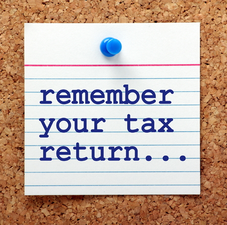 the end of the year: The words Remember Your Tax Return on a note card pinned to a cork notice board as a reminder to complete before the deadline