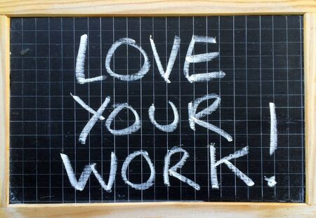 hand job: The words Love Your Work written by hand on a blackboard as a concept for employee and job satisfaction