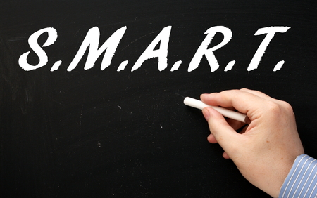 achievable: Male hand in a business suit writing the word SMART on a blackboard as a reminder to plan your goals in a specific,measurable,achievable,relevant and timely manner Stock Photo