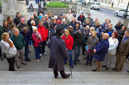 guia turistico: London, England - December 28, 2015: A man in a top hat and coat addresses a crowd of people as part of guided tour in Threadneedle Street, London Editorial