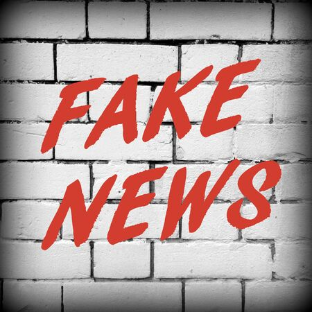 disinformation: The words Fake News in red text on a white brick wall as a reminder to be aware of hoaxes and disinformation for propaganda uses Stock Photo