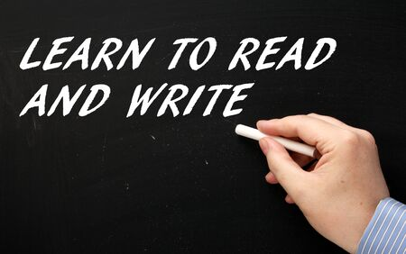 fundamentals: Hand writing the words Learn to Read and Write in white text on a blackboard as a reminder that education is a key to success