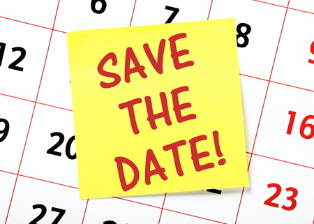 event calendar: The words Save The Date in red text on a yellow sticky note posted on a wall calendar as a reminder Stock Photo