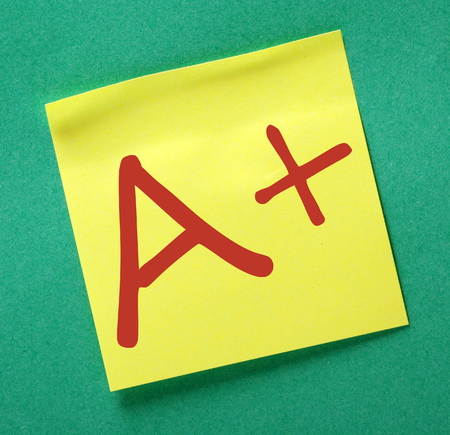 note board: A Plus grade for your work in red text on a yellow sticky note posted on a green bulletin board