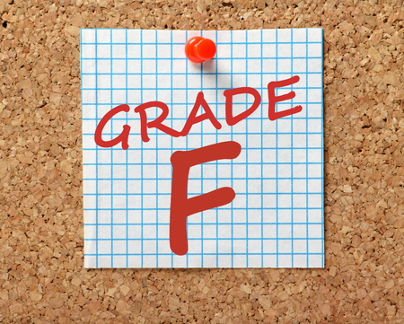 The words Grade F for fail in red text on a piece of squared graph paper pinned to a cork notice board Stock Photo
