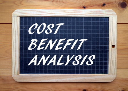 jargon: The words Cost Benefit Analysis in white text on a blackboard as a reminder to assess the strengths and weaknesses of a business proposition or opportunity