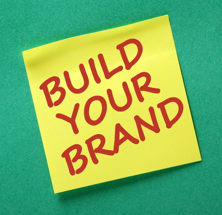 note board: The words Build our Brand in red text on a yellow sticky note posted on a green notice board as a reminder