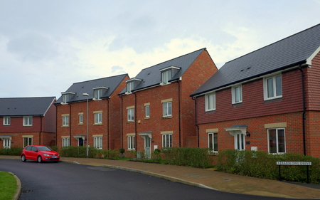Bracknell, England - Nov 20, 2017: Row of new build red brick homes on a street with a car in the town of Bracknell, England
