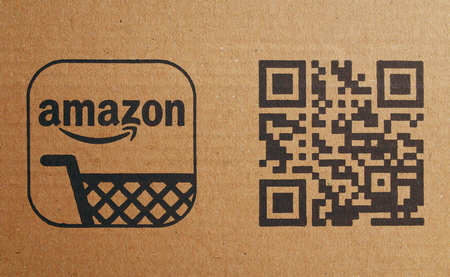 Bracknell, England - February 10, 2018: Close up of the Amazon company shopping trolley logo next to a QR or Quick Response bar code on brown cardboard packaging. Photographed in Bracknell, England Editorial