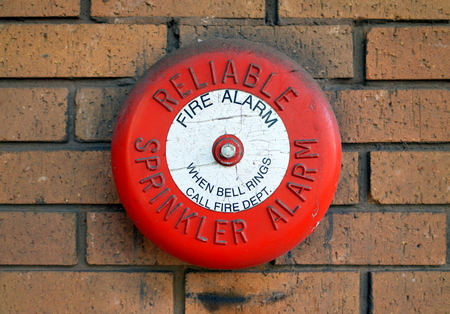 Bracknell, England - February 21, 2018: A Reliable Sprinkler Alarm Fire Alarm Bell on an external brick wall in England. The Reliable Automatic Sprinkler Co was founded in the USA in 1920
