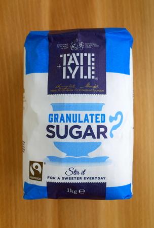 Bracknell, Inglaterra - 21 de febrero de 2018: Una bolsa de un kilo de azúcar granulada Tate & Lyle sobre un fondo de madera. Henry Tate y Abram Lyle fusionaron sus respectivos negocios azucareros en Londres en 1921. Editorial