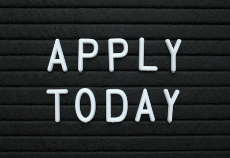 The phrase Apply Today in white plastic letters on a black letter board as a reminder