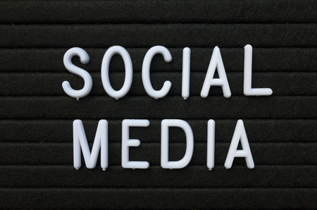 The words Social Media in white plastic letters on a black letter board