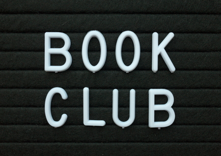 The words Book Club in white plastic letters on a black letter board as a reminder of an event for avid readers and book worms Archivio Fotografico - 108297184