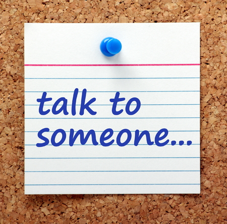 Advice to Talk To Someone written on a card pinned to a cork notice board as a reminder to share your problems Stock Photo