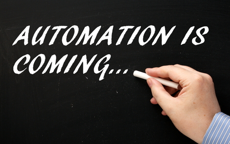Hand writing the phrase Automation is Coming on a blackboard as a reminder for business and workers to prepare and plan ahead Stock Photo